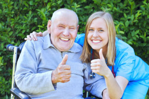 senior man with his caregiver raising their thumb