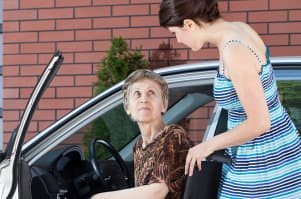 a photo of a woman helping a senior woman ride her car