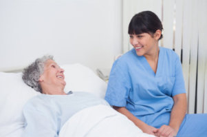 a photo of a senior woman on bed while talking to her nurse
