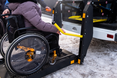 a man presses a button on the control panel to pick up a woman in a wheelchair in a taxi for the disabled