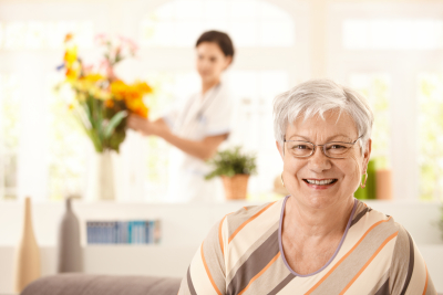 portrait of happy elderly women sitting on sofa at home, nurse arranging flowers in background.